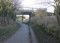 High Harrington station on the Cleator & Workington Junction Railway, seen in March 2018. This view looks towards Distington along the established trackbed cycle path. The remains of the Workington platform, which last saw passengers in 1931, can be seen on the right. Goods trains continued to pass through until 1964. The central bridge pier is a later addition supporting the heavy road traffic that passes over today. [Ref query 14 March 2018] <br><br>[Mark Bartlett&nbsp;09/03/2018]