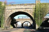 Looking north along Edinburgh's Inglis Green Road on Sunday 25 March 2018 through one of the arches of the 1822 Slateford Aqueduct carrying the Union Canal. Just beyond stands the 1848 railway viaduct, being crossed at the time by the TransPennine 0915 Edinburgh Waverley - Manchester Oxford Road.<br><br>[John Furnevel&nbsp;25/03/2018]