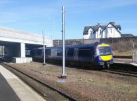 A Stirling to Glasgow service halts, as required, at the southern end of the Platform at Larbert on 20 March. The large gap between the tracks allows the OHLE masts to be installed there, rather than on the platforms which is presumably a more expensive and less safe option.<br> <br><br>[David Panton&nbsp;20/03/2018]