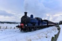 The Strathspey Railway's Santa Express, hauled by Caledonian Railway 0-6-0 No.828, runs towards Broomhill on 11th December 2017. Part of the snow covered Cairngorms can be seen in the background and, yes, it was as cold as it looks!.<br> <br><br>[John Gray&nbsp;11/12/2017]