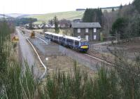 ScotRail 170454 passing between the abandoned former station house and the Network Rail compound at Fountainhall on 22 March 2018 with the 0930 Tweedbank - Edinburgh. Fountainhall village stands in the background. <br><br>[John Furnevel&nbsp;22/03/2018]