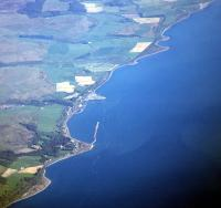 Aerial view over Cairnryan looking south showing the former Military Port. Its associated railway ran along the coastline from Leffnol (top) to Cairn Point (bottom). The triangular shape of the modern day ferry terminal can also be seen just left of centre extending out into the Loch.<br><br>[Ewan Crawford //]