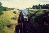 Approaching Mossend Marshalling Yard from the north is a 47 hauled passenger train. It is about to pass under the A8.<br><br>[Ewan Crawford&nbsp;//1987]