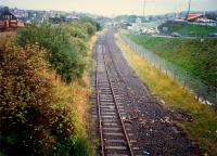 Looking west to Airdrie station (distant 303 in bay platform). In distant left the former Caley line crosses a bridge, then crossed the NB line by means of a missing bridge and terminated at a station in the carpark to the right.<br><br>[Ewan Crawford&nbsp;//1987]