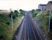 Looking south near Carfin on the Wishaw Deviation Line. Jenny Lind siding was just beyond the distant overbridge. The distant works is a BOC works - convenient for Ravenscraig.<br><br>[Ewan Crawford&nbsp;//1987]