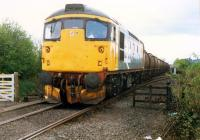 26 with a Molasses train crosses the level crossing at Cambus Junction.<br><br>[Ewan Crawford&nbsp;//1988]