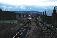 Westbound train passes bonded warehouses west of Keith.<br><br>[Ewan Crawford&nbsp;//]