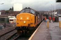 Separating 37 416 from its train at Kyle of Lochalsh in order to run round. Two walkers try to blend in with the high visibility jackets.<br><br>[Ewan Crawford 03/01/1989]