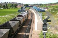 Coal empties from Longannet passing through Dunfermline Queen Margaret on their way back to Hunterston in June 2006 shortly after reversal in Halbeath sidings. The trackbed of the former S&DR route to Alloa and Stirling is on the right. [See image 46494]<br><br>[John Furnevel&nbsp;13/06/2006]