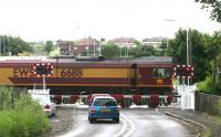 EWS 66118 on Halbeath level crossing in June 2006 in the process of running round the coal train which it has just dropped in Halbeath sidings. The remains of Halbeath station are just off picture to the right. <br><br>[John Furnevel&nbsp;13/06/2006]