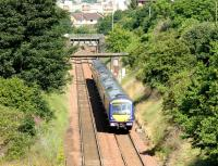 A diverted Glasgow - Edinburgh service passes through Slateford on the sub on 16 July 2006. The train has just passed below the bridge that carried the Caledonian main line out of Princes Street and which now serves as vehicle access from Merchiston to Slateford sidings and PW depot. The deck of the bridge carrying the current line between Slateford station and Haymarket can be seen just beyond.<br><br>[John Furnevel&nbsp;16/07/2006]